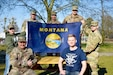 "Clockwise from left, seated: Maj. Colin Curry, Spc. Dylan Roselles, Maj. Brian Casey, 1st Sgt. Alicia Roethler, Sgt. Colton Smith, Sgt. 1st Class John Proulx, and Pfc. Koleton Grimes, all Soldiers from the 652nd Regional Support Group out of Helena, Montana, pose with the Montana state flag April 6, 2020 on ""406"" day in Powidz, Poland. The Montana Soldiers with the 652nd RSG are wrapping up a nearly year-long deployment to Poland by quarantining at North Fort Hood, Texas. (U.S. Army Reserve photo by Maj. Olha Vandergriff, 652nd Regional Support Group)"
