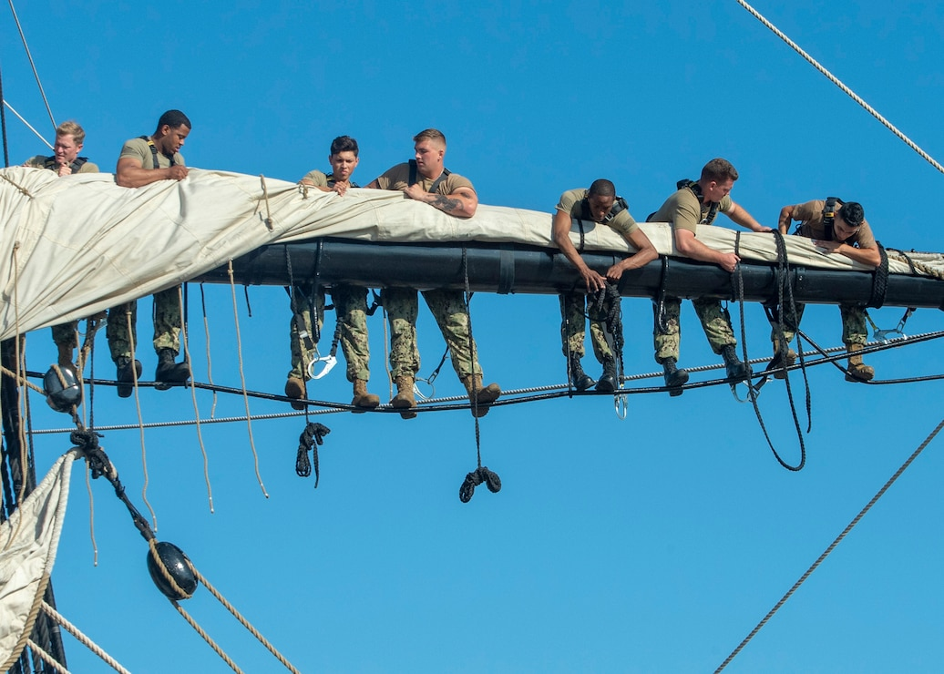 group of sailors hanging around on the sails