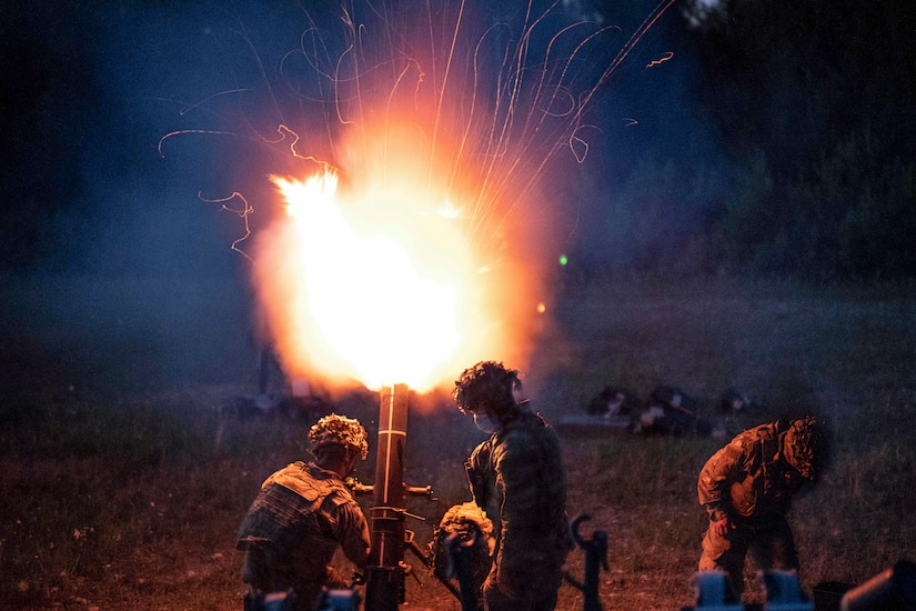 Soldiers fire an illumination round from a mortar system, lighting up a dark sky.