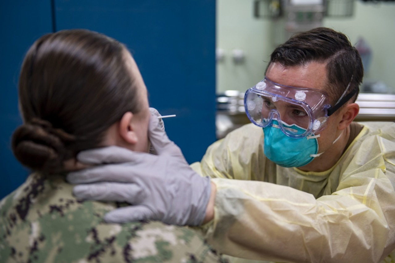 A female sailor is tested for COVID-19 by a health care provider wearing personal protective equipment.