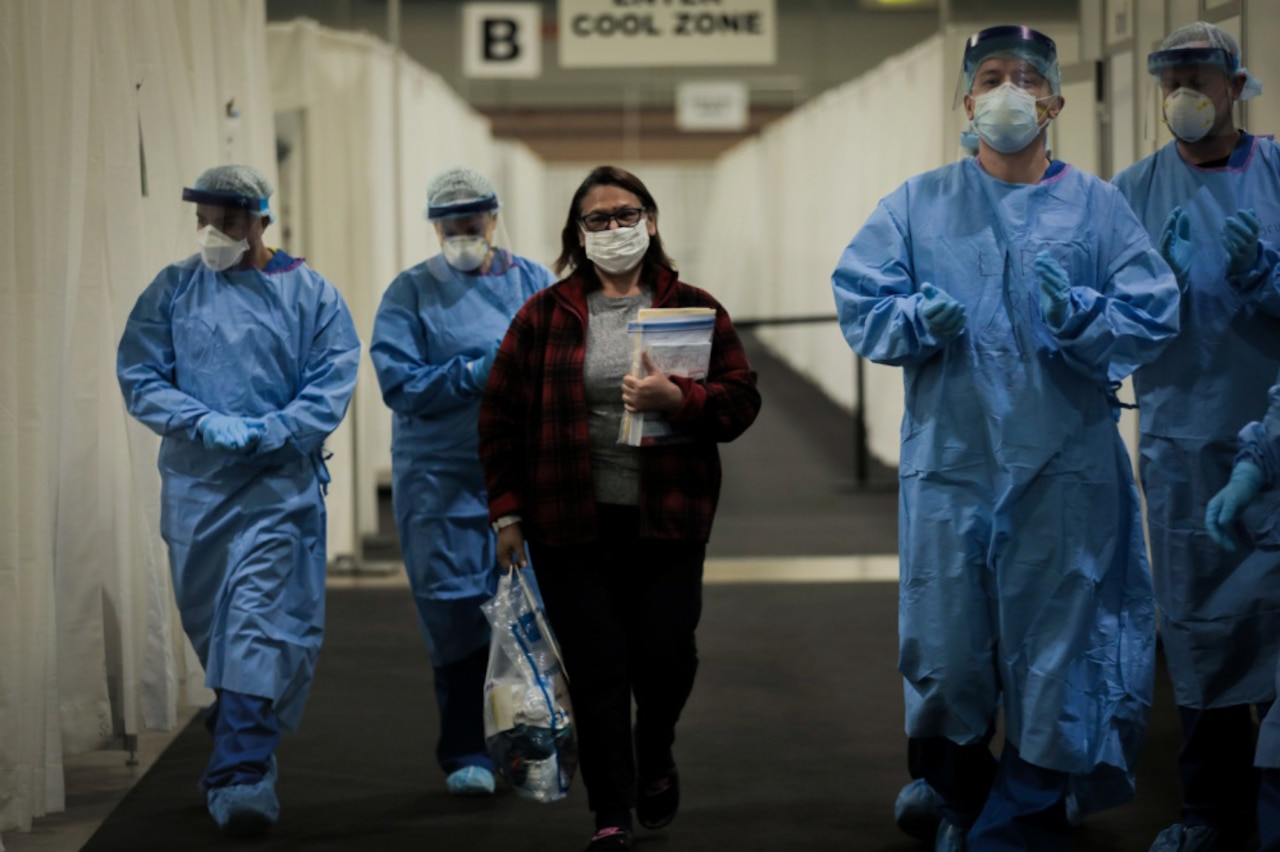 Flanked by four medical providers wearing personal protective gear, a woman leaves a field hospital.
