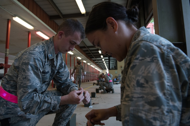 An Air Force Reserve Officer Training Corps cadet helps a fellow cadet load a handgun magazine July 9, 2020, at the Combat Arms Training and Maintenance range on Maxwell Air Force Base, Alabama.