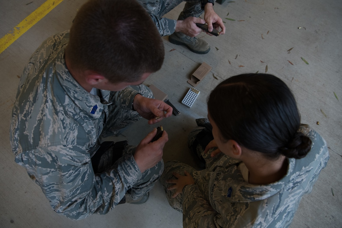 An Air Force Reserve Officer Training Corps cadet demonstrates to a fellow cadet how to properly load ammunition into her handgun's magazine July 9, 2020, at the Combat Arms Training and Maintenance range on Maxwell Air Force Base, Alabama.