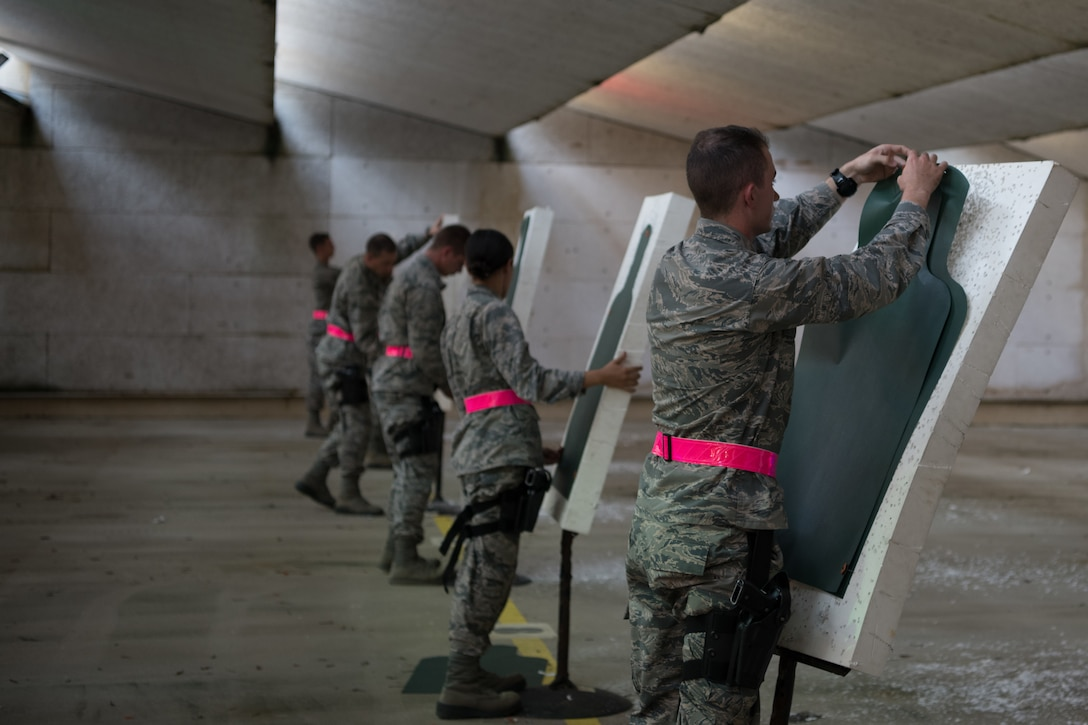 Air Force Reserve Officer Training Corps cadets retrieve their paper targets and replace them with new paper targets after completing their weapons qualification July 9, 2020, at the Combat Arms Training and Maintenance range on Maxwell Air Force Base, Alabama.
