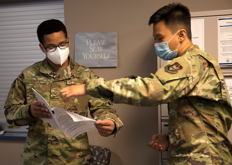 Two airmen wearing masks while holding paper