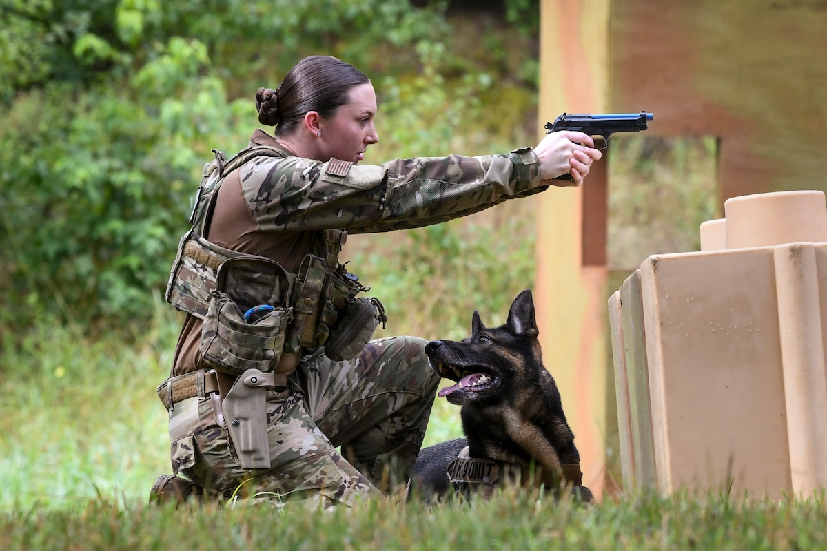 An airman kneeling in grass aims a pistol, as a dog lies next to her and stares attentively.