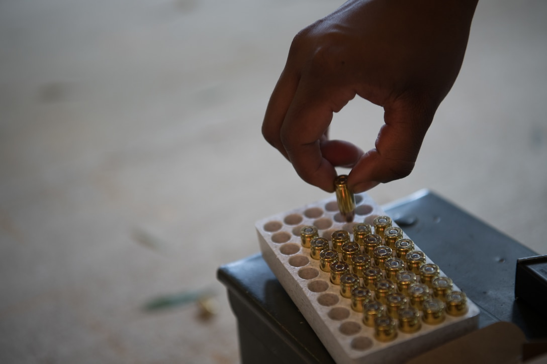 An Air Force Reserve Officer Training Corps cadet removes ammunition from a case while loading a Beretta M9 pistol before qualifying July 9, 2020, at the Combat Arms Training and Maintenance range on Maxwell Air Force Base, Alabama.