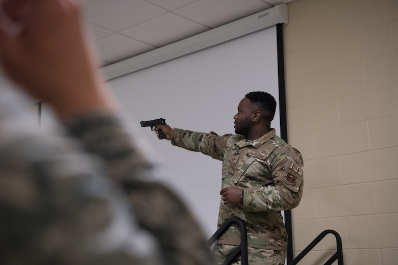 Staff Sgt. David Ikner demonstrates how to handle a Beretta M9 pistol safely with a class of cadets from the Air Force Reserve Officer Training Corps July 9, 2020, at the Combat Arms Training and Maintenance facility on Maxwell Air Force Base, Alabama.