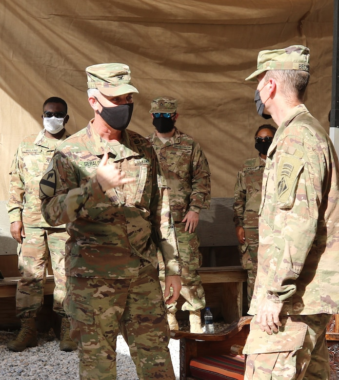 Members of the Afghanistan District watch as Colonel Mark Geraldi bids farewell to Colonel Chris Becking as he completes his tour as the outgoing commander.