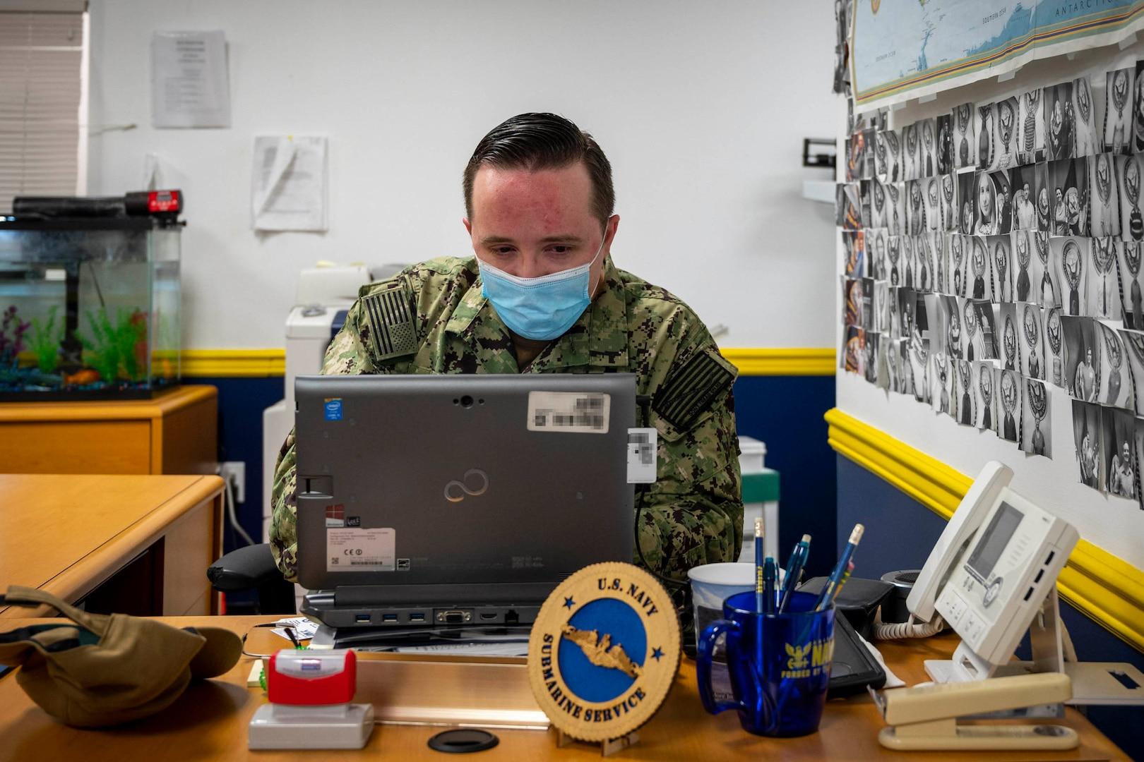 Masked sailor works on laptop.
