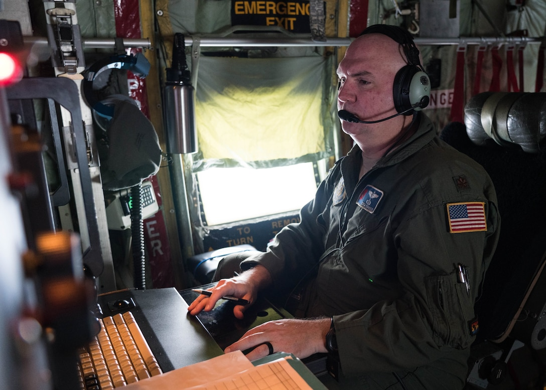 Maj. Tobi Baker, 53rd Weather Reconnaissance Squadron aerial reconnaissance weather officer, reviews weather data collected while flying in Hurricane Douglas July 26, 2020. The Air Force Reserve Hurricane Hunter aircrew flew into the first hurricane of the Pacific season to collect weather data to assist the Central Pacific Hurricane Center with their forecasts. The 53rd WRS, assigned to the 403rd Wing at Keesler Air Force Base, Mississippi, departed July 22 to conduct operations out of Barbers Point Kapolie Airport, Hawaii. (U.S. Air Force photo by Lt. Col. Marnee A.C. Losurdo)