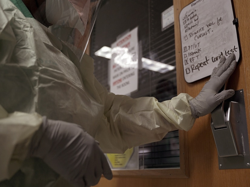 A medical professional wearing protective gear opens a hospital room door with patient notes on the door.