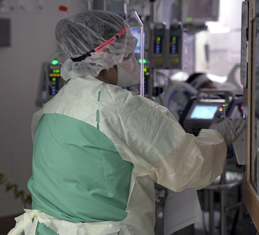 A nurse enters a patient room in a COVID-19 intensive care unit.
