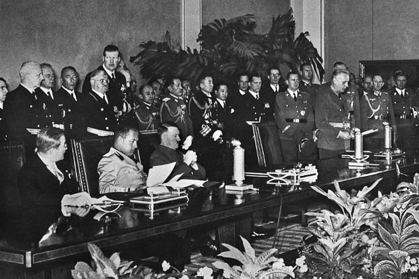Three men in military uniforms sit behind a long table with lots of people standing behind them.