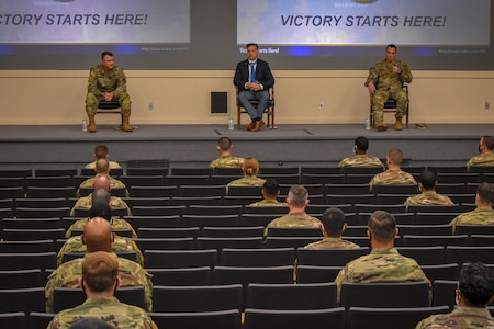 army soldiers sit in a mostly empty theater listening to 3 men speaking on stage.