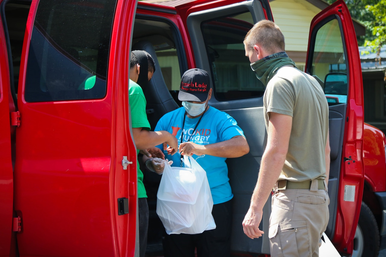 Two soldiers wearing face masks and civilian clothes flank a woman as she receives a white plastic bag containing meals.