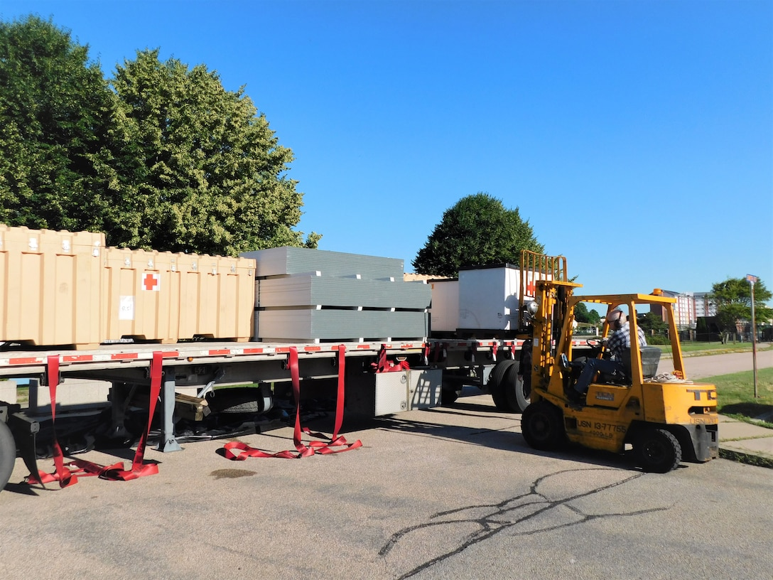 Steve Stringham, NMRTC clinic staff member, operates the forklift to offload shelters after their arrival in Newport. The Defense Logistics Agency partnered with Air Force and Navy medical to provide shelters for COVID-19 screening at naval medical facilities in the Northeast.
