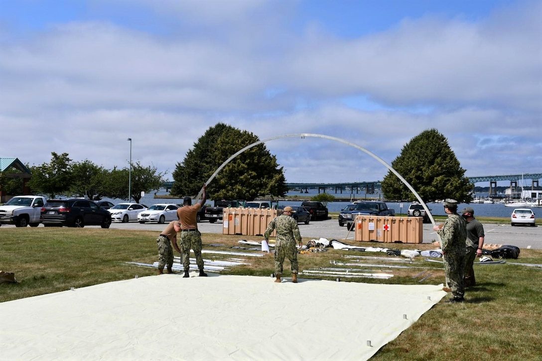 NMRTC employees raise the first of five shelters at the Navy's medical clinic in Newport, Rhode Island, on July 7, 2020. The Defense Logistics Agency partnered with Air Force and Navy medical to provide shelters for COVID-19 screening at naval medical facilities in the Northeast.