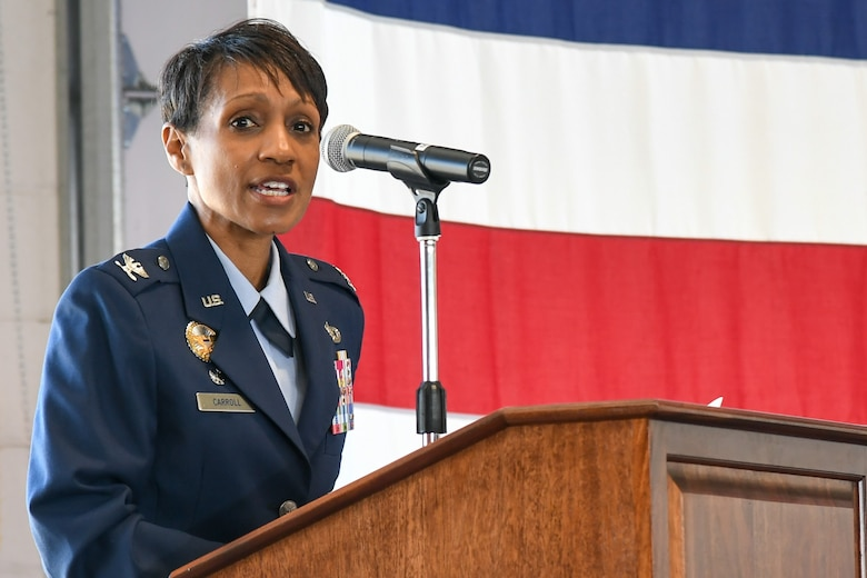 Col. Jenise M. Carroll speaks from behind a podium during her assumption of command of the 75th Air Base Wing.