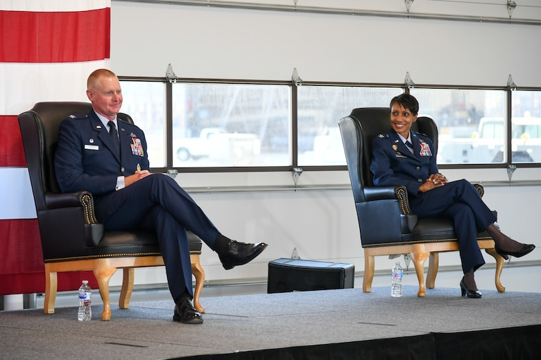 Col. Jenise M. Carroll, right, and Col. Jon A. Eberlan seated on stage during the 75th Air Base Wing change of command ceremony.