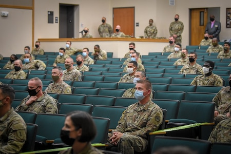 groups of soldiers sit in an mostly empty theater listening to 3 men speak on the stage.
