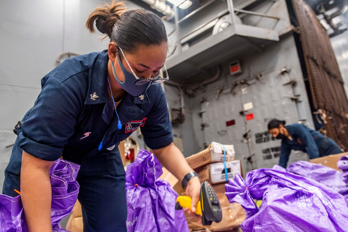 Sailors wearing protective gear sort through packages.