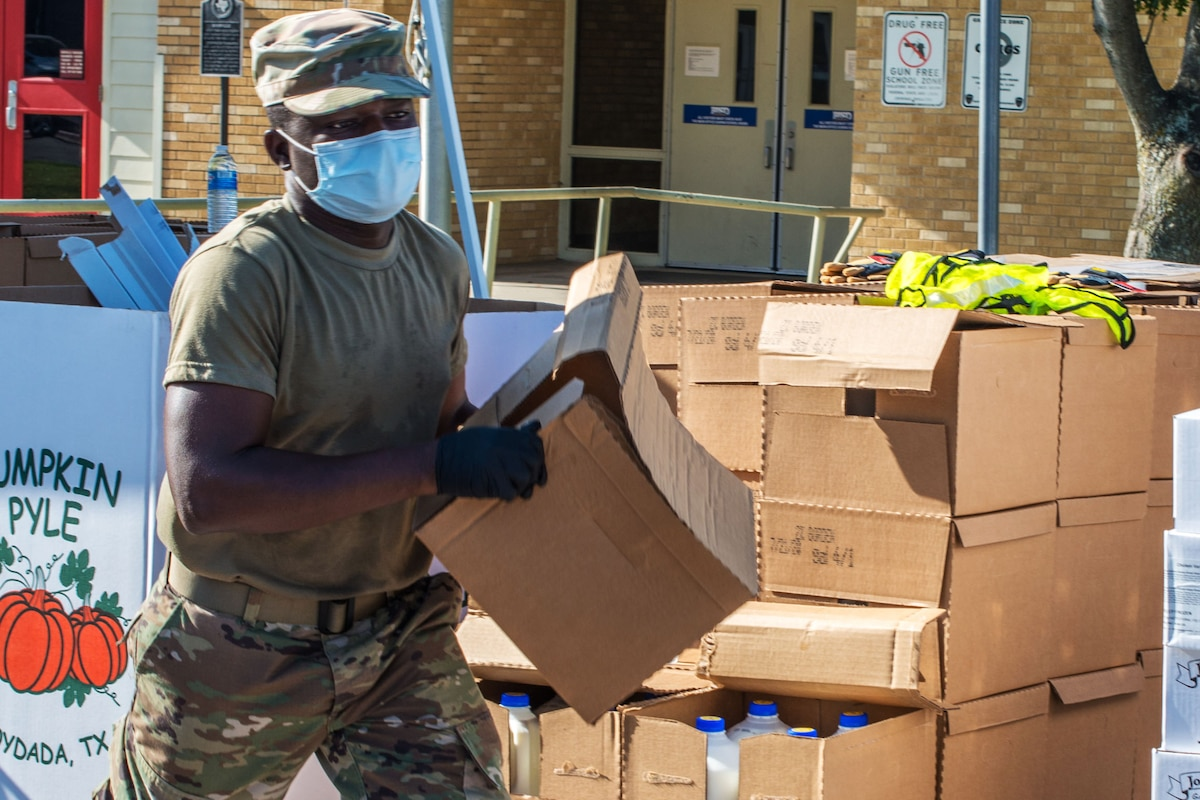 A guardsman wearing personal protective equipment carries a box of food as part of the final scheduled food distribution.