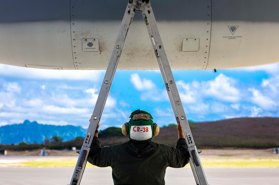 A Marine standing between the legs of a two-sided ladder looks up at an aircraft.