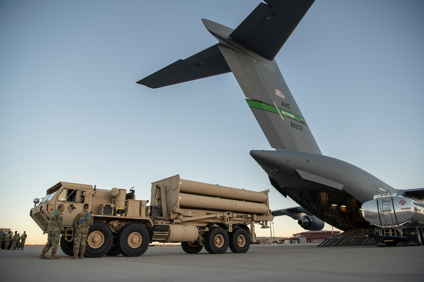 A large truck backs onto a large cargo aircraft.