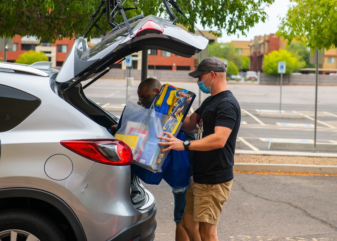 Brandon Wright, Back to School Bash volunteer and 56th Equipment Maintenance Squadron sheet metals technician, loads school supplies and toys into a car July 23, 2020, at the Gila Bend Arena in Glendale, Ariz.