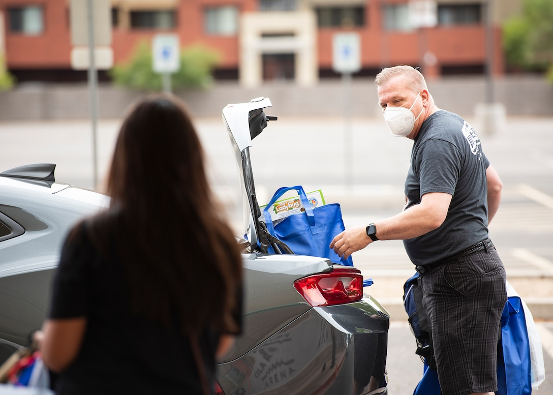 Jimbo Norton, Back to School Bash volunteer and 56th Communication Squadron resource advisor, loads a car during the Back to School Bash drive-thru July 23, 2020, at the Gila Bend Arena in Glendale, Ariz.