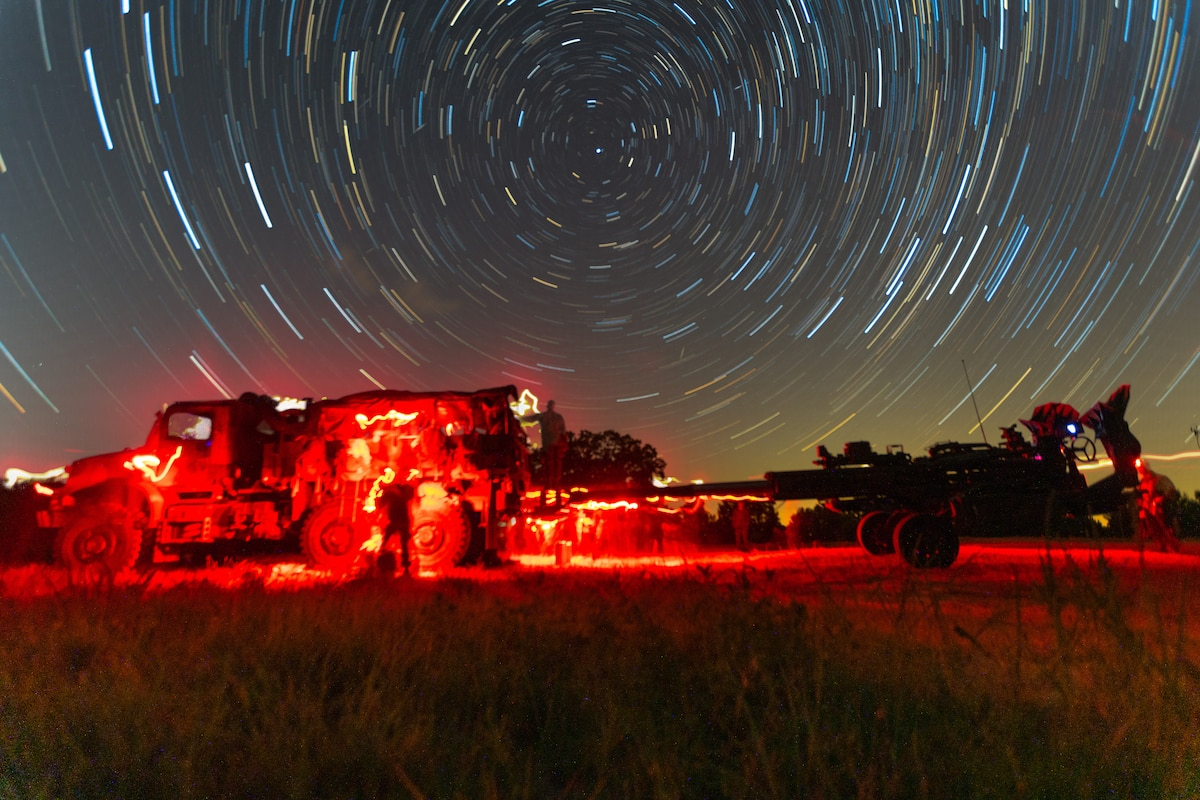 Marines work on vehicles bathed in red light.