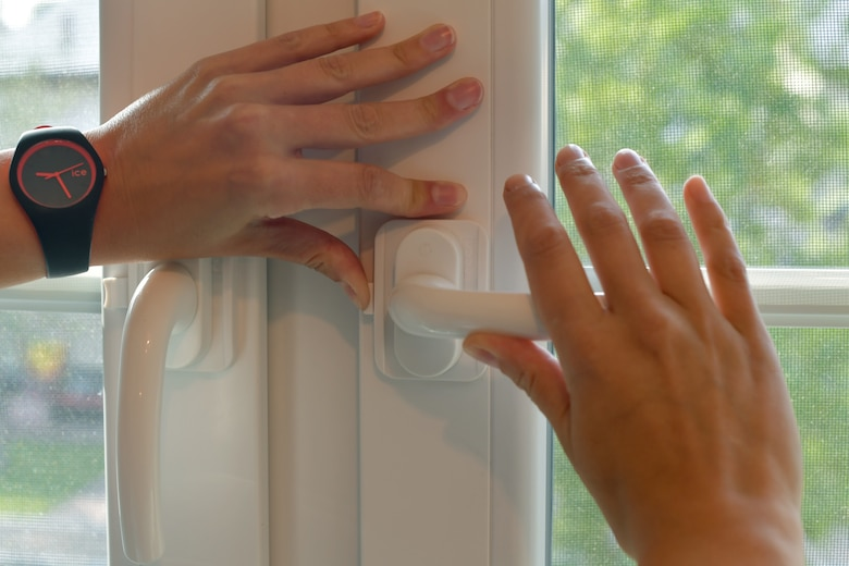 A person's hands turning the handle to open a window.