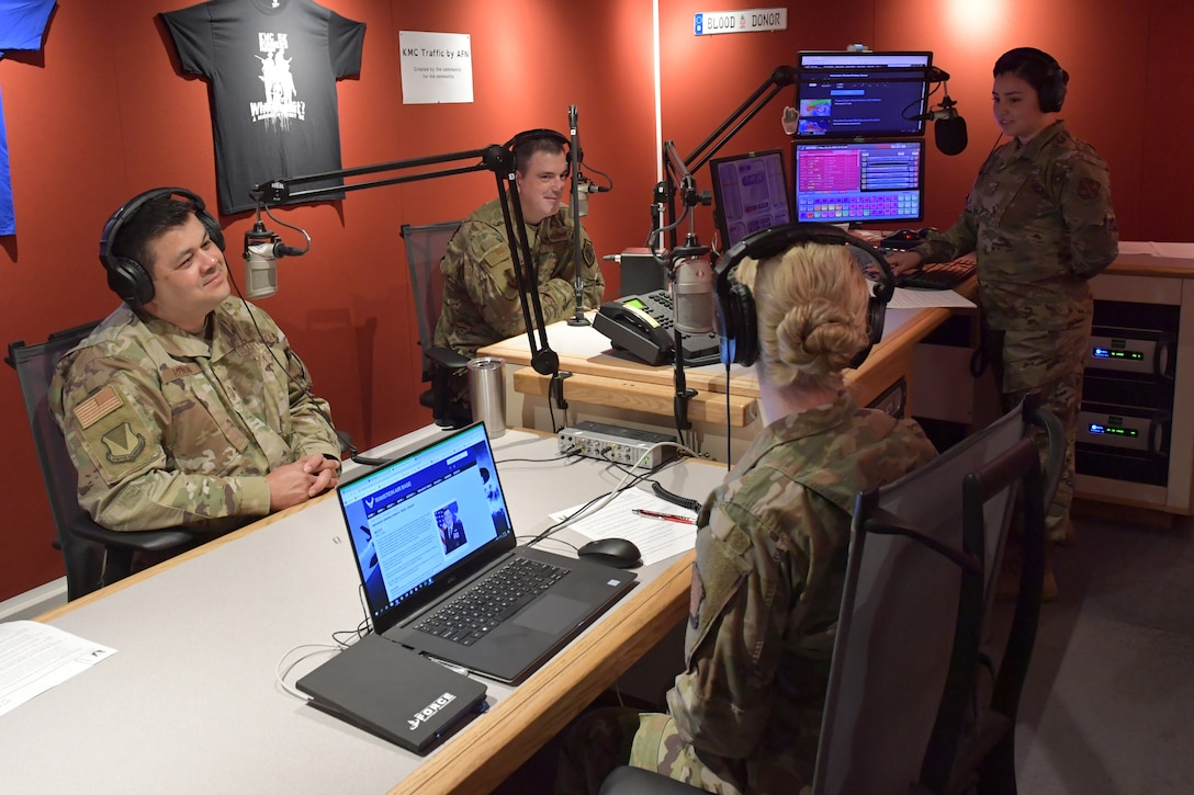 A group of Airmen sitting and standing in a radio station studio.