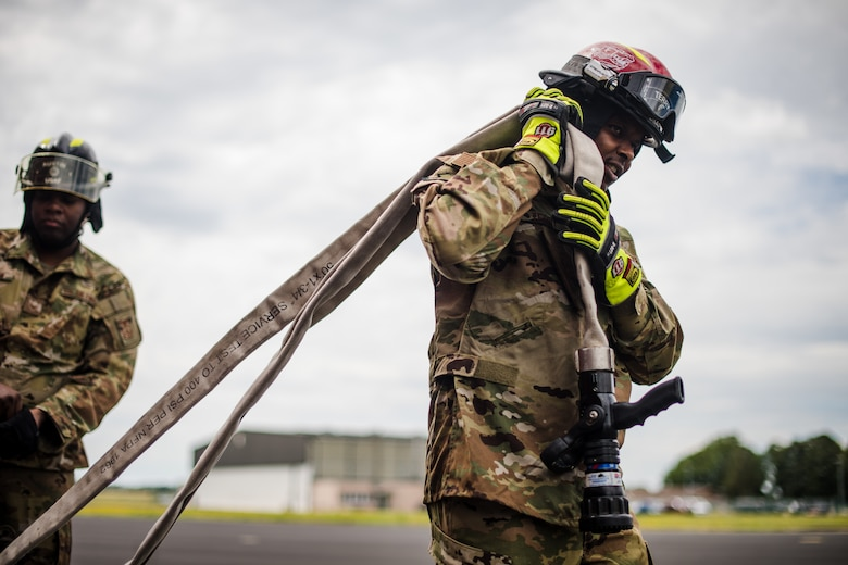 Photo of Air Force firefighter carrying hose