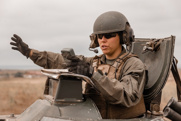 U.S. Marine Sgt. Chelsea Romanowiz, a student with the Assault Amphibian Vehicle Commander Course, Assault Amphibian School, directs a fellow Marine during mounted land navigation training in the Oscar Two Training Area on Marine Corps Base Camp Pendleton, California, July 22, 2020. The Vehicle Commander Course is used to train intermediate level Marines on the responsibilities of an AAV commander, with a focus on crew gunnery, direction and supervision. Romanowiz is a native of Jacksonville, Florida. (U.S. Marine Corps photo by Lance Cpl. Alison Dostie)