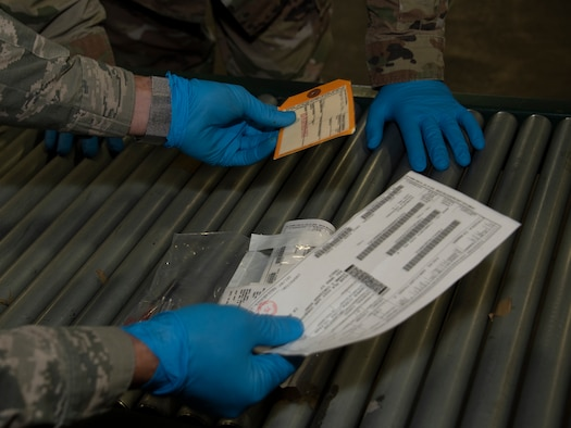 U.S. Air Force Airman 1st Class Yaser Belal, left, 60th Aerial Port Squadron packing and crating technician, shows Chief Master Sgt. Robert Schultz, 60th Air Mobility Wing command chief, the various labels that are affixed to shipment containers during Leadership Rounds July 24, 2020, at Travis Air Force Base, California. The 60th APS is the United States Transportation Command's primary west coast aerial port providing global and passenger distribution for the United States and its Allies. The Leadership Rounds program provides 60th AMW leadership an opportunity to interact with Airmen and get a detailed view of each mission performed at Travis AFB. (U.S. Air Force photo by Heide Couch)