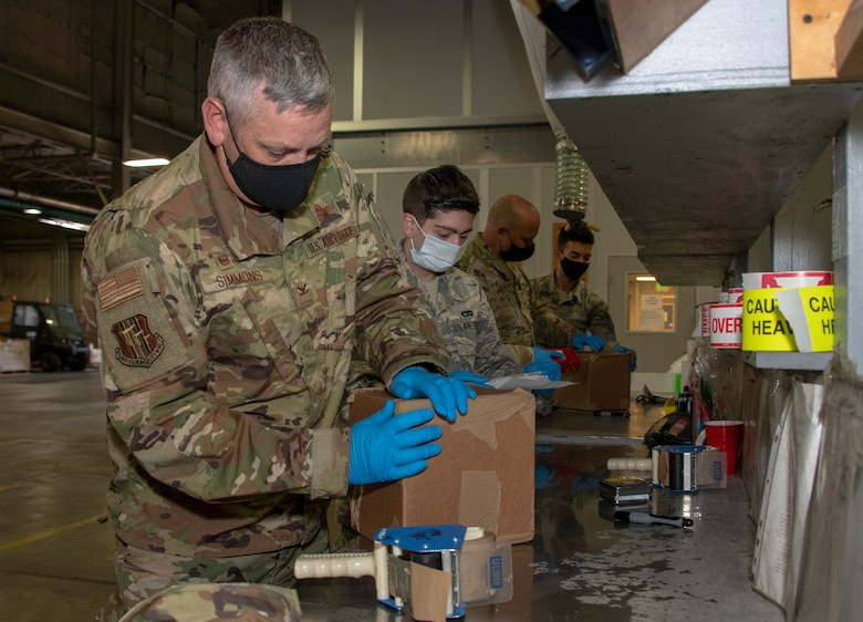 From left, U.S. Air Force Col. Corey Simmons, 60th Air Mobility Wing commander, Airman 1st Class Gregory Concilla, 60th Aerial Port Squadron packing and crating technician, Chief Master Sgt. Robert Schultz, 60th AMW command chief, and A1C Yaser Belal, 60th APS packing and crating technician, participate in a packing and crating demonstration during Leadership Rounds July 24, 2020, at Travis Air Force Base, California. The 60th APS is the United States Transportation Command's primary west coast aerial port providing global and passenger distribution for the United States and its Allies. The Leadership Rounds program provides 60th AMW leadership an opportunity to interact with Airmen and get a detailed view of each mission performed at Travis AFB. (U.S. Air Force photo by Heide Couch)