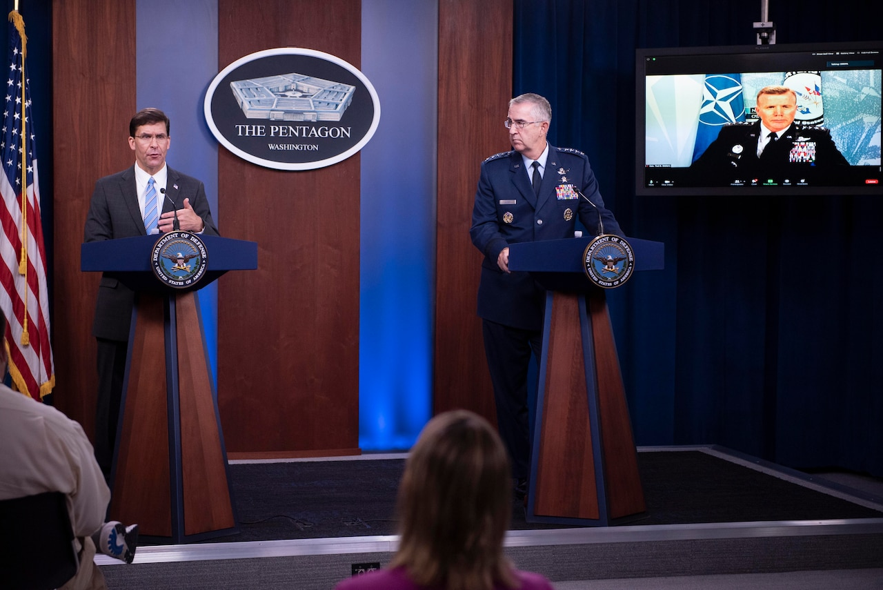 Two men stand behind lecterns while a third man in a military uniform appears on a television screen.