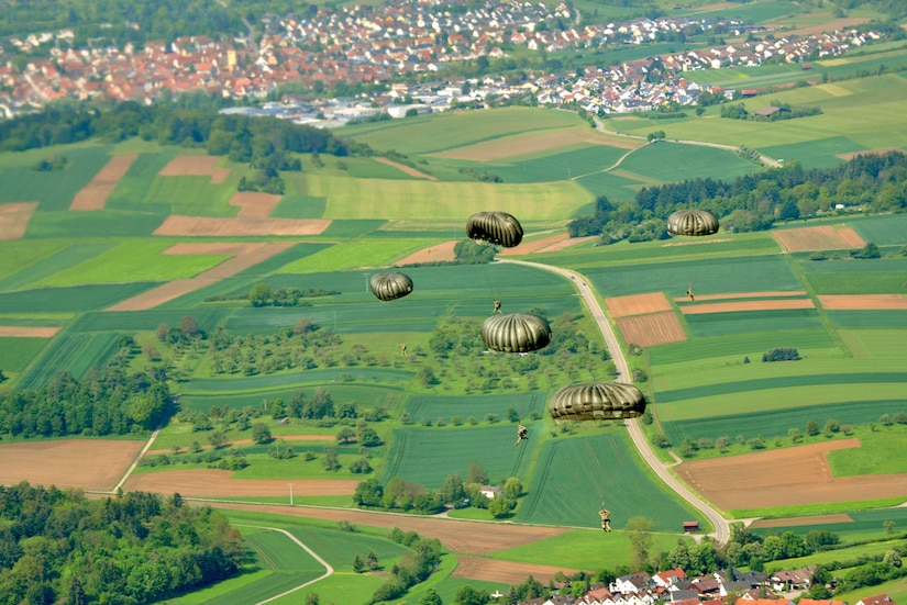 Service members parachute over lush green fields.