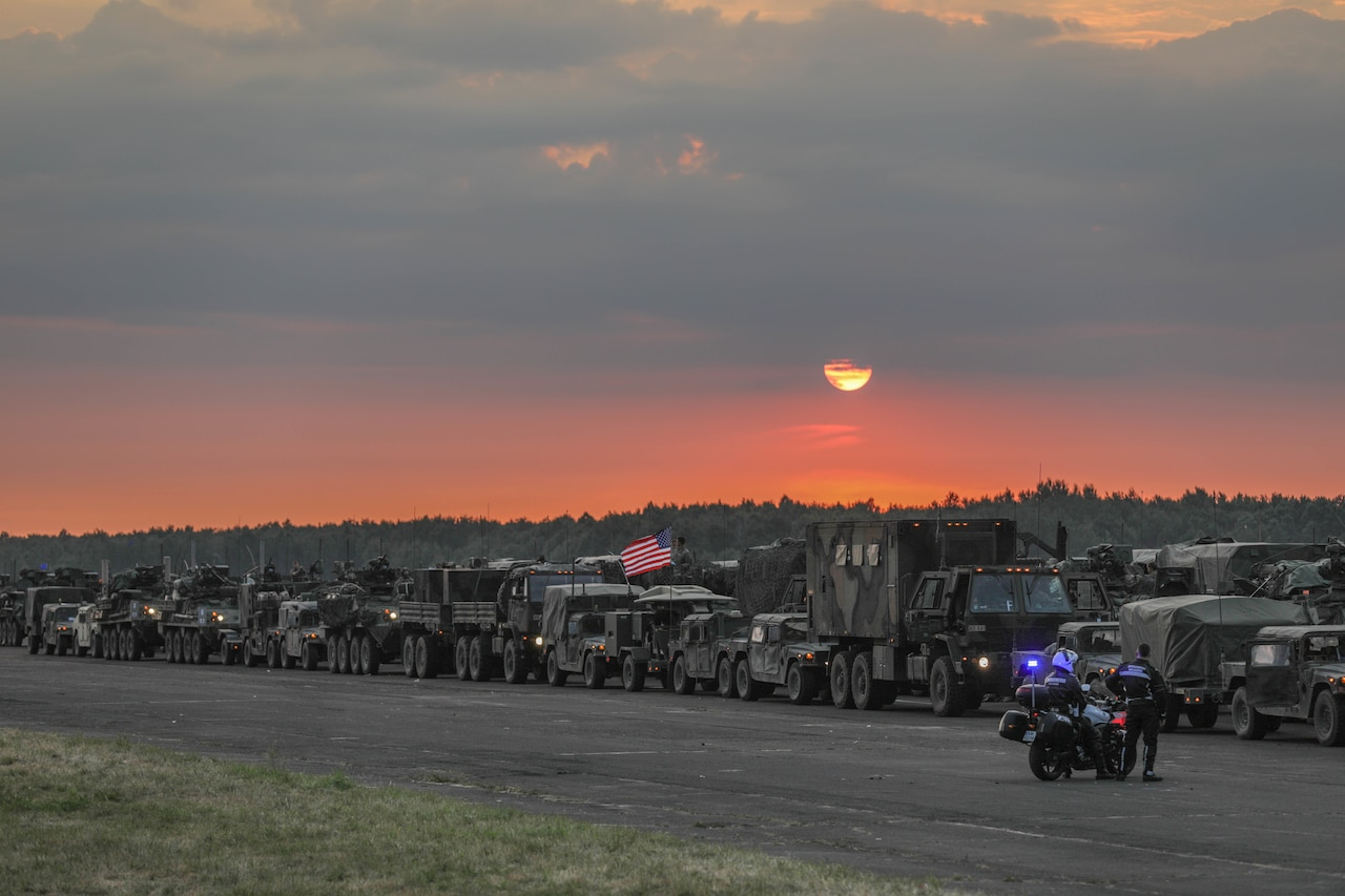 More than a dozen military vehicles line up on a road at dusk.