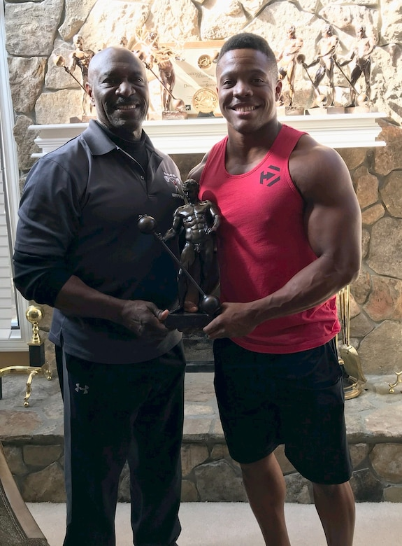 Staff Sgt. Geremy Satcher takes a photo with eight-time Mr. Olympia, Lee Haney as they hold one of his trophies. Haney became a mentor for Satcher when he was a body builder.