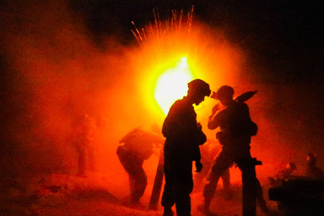Soldiers fire a weapon illuminated by an orange light.