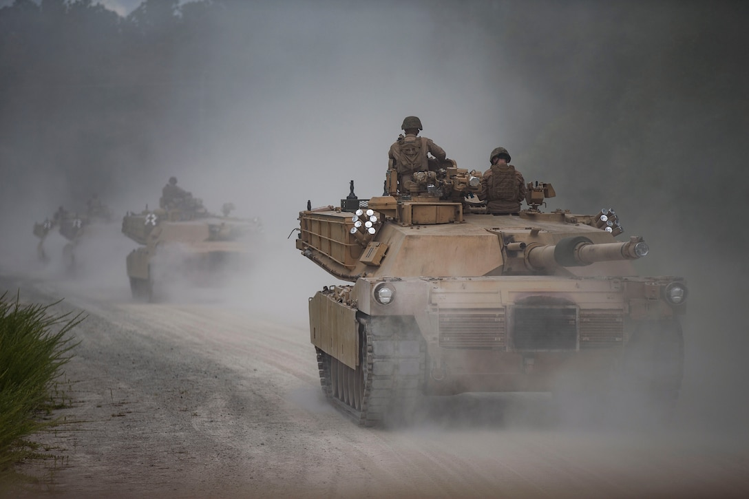 Marines ride tanks in a line surrounded by fog.