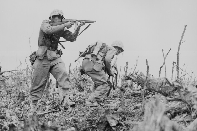 A Marine aims his weapon while another Marine looks for cover.