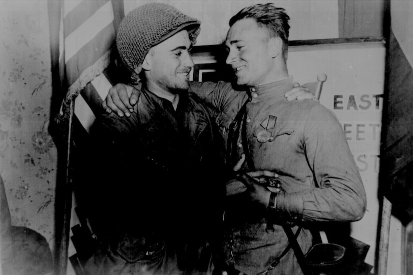Two men in military uniforms smile at each other.