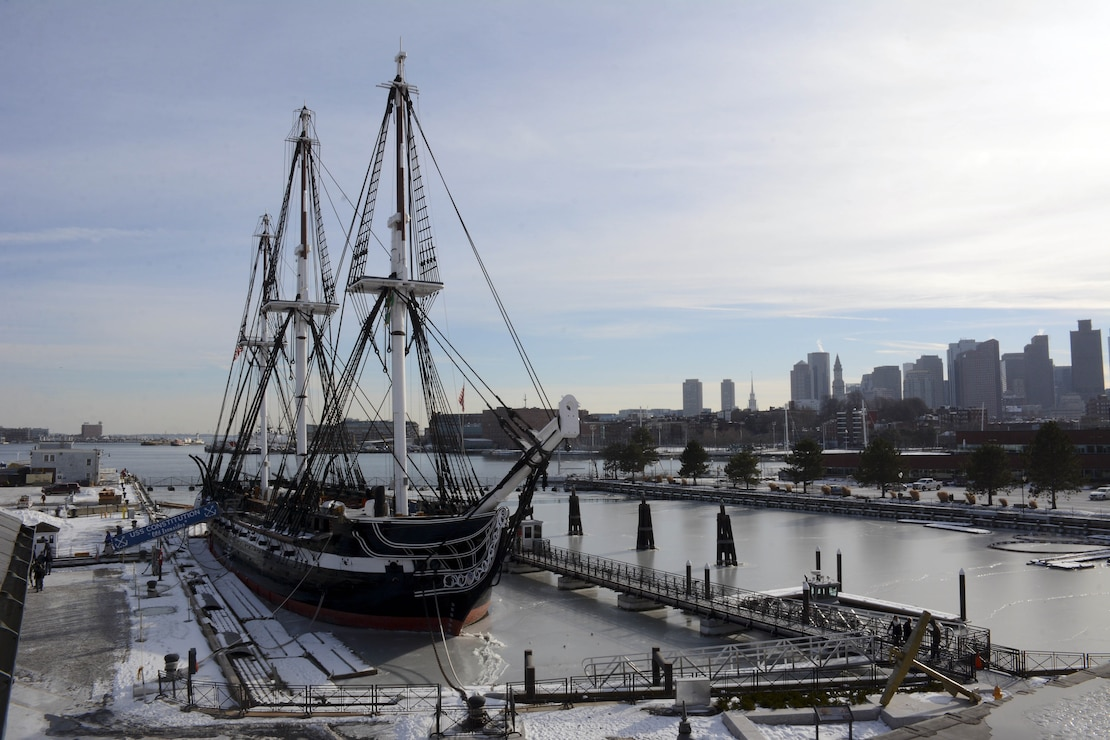 USS Constitution sits moored pier side at Boston Navy Shipyard with boston skyline in the background