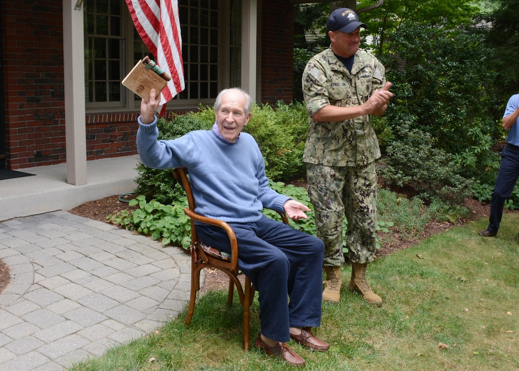 Capt. Thomas J. Hudner sitting in a chair shows off his birthday gift, a plaque made of USS Constitution wood and copper