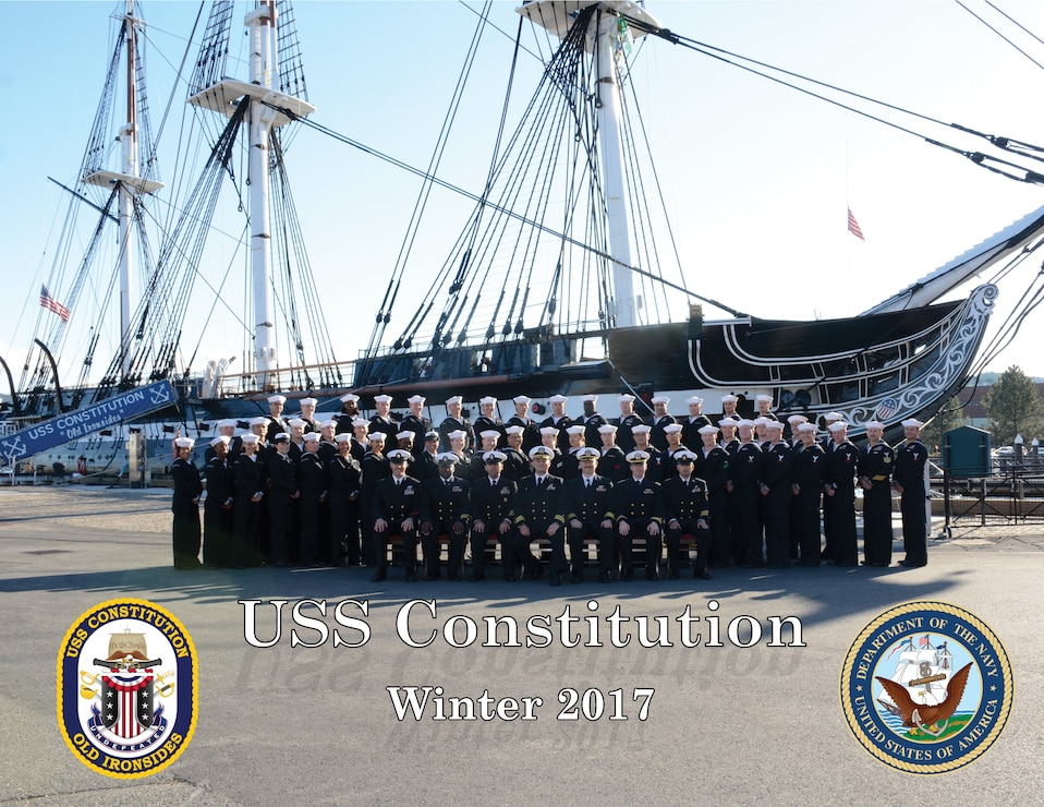 USS Constitution's crew poses for the 2017 command winter photo front of docked ship