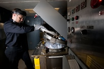 Peter Mech, an engineer at Naval Surface Warfare Center, Carderock Division operates the Plastic Waste Processor on July 23, 2015.
